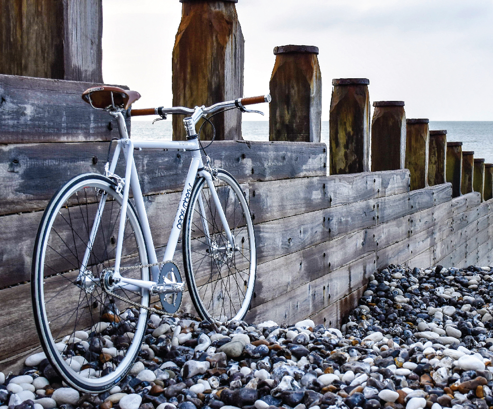 Bike stands on a pebbled surface and leans against a wooden fence.